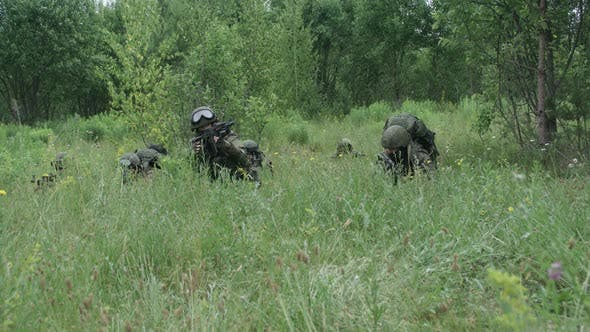 Soldiers in Camouflage with Assault Rifles Out of the Ambush in the Field Military Action in the