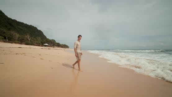 Young Attractive Man Walking on the Wet Sand Into the Ocean Swell in the Beach in Uluwatu Bali and