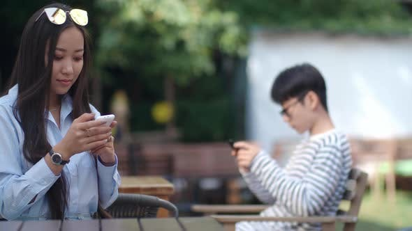 Thumbnail for Asian Girl Typing on Smartphone in Outdoor Cafe