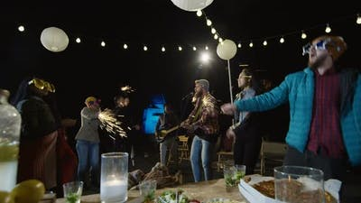 People Dancing with Sparklers on a Rooftop