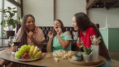 Multiracial Women Playing Board Game Drinking and Relaxing Indoors