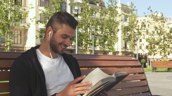 Thumbnail for A Happy Guy Is Reading a Book in a City Alley