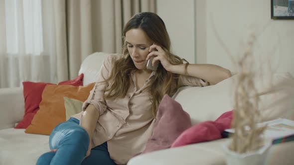Thumbnail for Happy Woman Call Phone on Sofa at Home. Smiling Woman Talking Mobile Phone