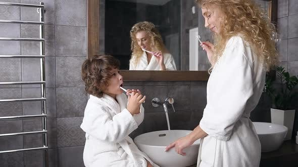 Cover Image for mother with curly hair and her dark-haired son in white robes brushing their teeth near the bathroom