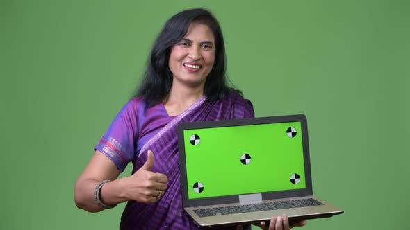 Cover Image for Mature Happy Beautiful Indian Woman Showing Laptop and Giving Thumbs Up