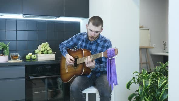 Thumbnail for Handsome young musician play acoustic guitar and emotionally singing lyric song at home