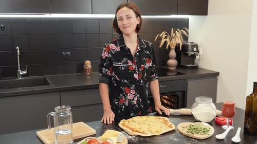 Woman takes out baked cheese pizza from oven, puts on wooden table and smiling at camera.