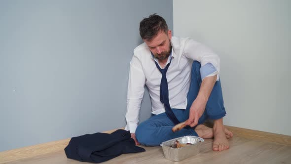 Thumbnail for Upset Bearded Man in Untidy Formal Clothes Is Sitting in an Empty Apartment. He Has Nothing To Eat