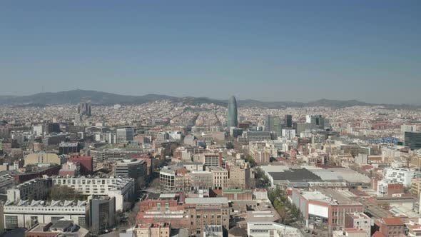 AERIAL: Barcelona Wide Drone Shot of City Towards Center with La Sagrada Familia and Torre Glories