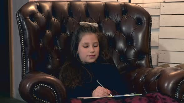 Thumbnail for Small Pretty Girl Painting a Picture Sitting in a Leather Armchair