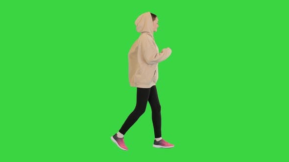 Young Female Runner in Hoody is Jogging on a Green Screen Chroma Key