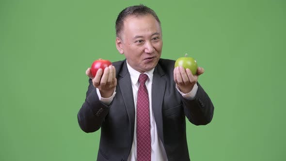 Thumbnail for Mature Japanese Businessman with Apples