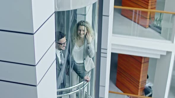 Thumbnail for Businesswoman and Businessman Riding Glass Elevator