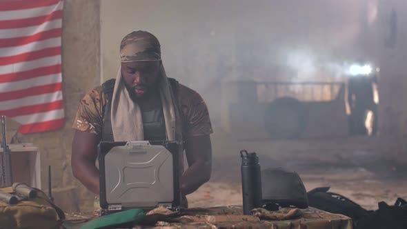Black Military Man Using Laptop and Radio at Base