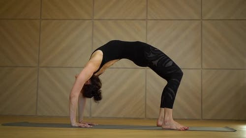 Young Charming Woman Practicing Yoga at Light Minimalist Studio Class Room