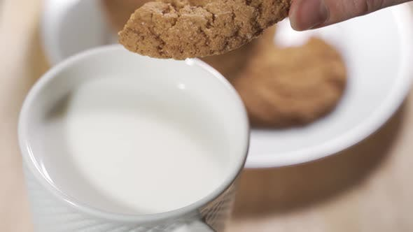 Thumbnail for A Woman Hand Dunks a Cookie in the Milk Mug During the Breakfast in a Warm Morning.