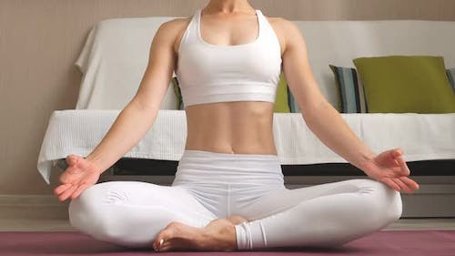 Young Woman Is Practicing Yoga at Home Relaxing in Simple Body Position Sitting on Floor.