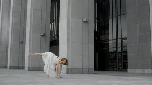 Young Balerina in White Dress are Doing Ballet Pa Outdoors Between the Columns of the Building 120
