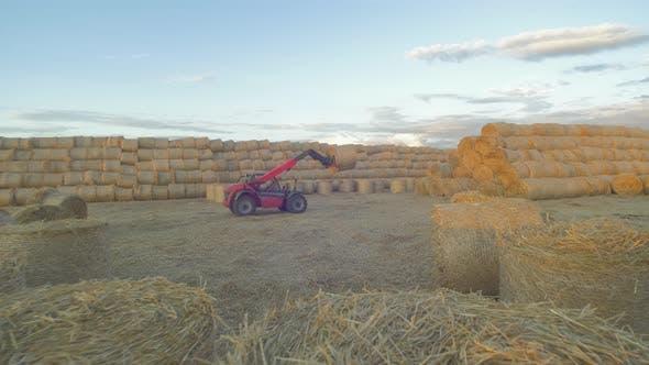 Picking up bales of hay