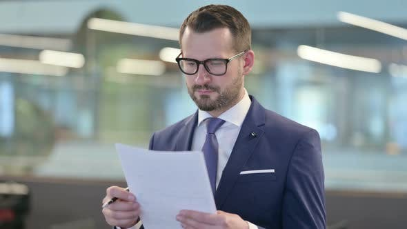 Thumbnail for Portrait of Middle Aged Businessman Reading Documents