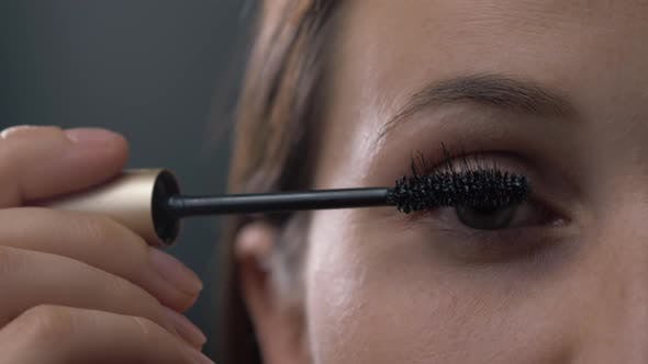 Cover Image for Close Up Shot of Young Woman Applying Mascara on Eyelashes Against Black Background