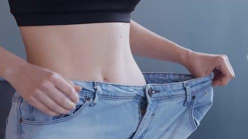 Erfolgreiche Weight Loss Frau mit Jeans zu Hause