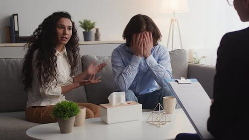 Young Married Couple Arguing and Quarreling During Personal Consultation with Marital Specialist