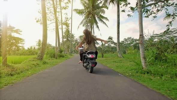 Couple Riding Their Scooter Through Forest. Life Style Idea Concept. Young Beautiful Couple Rides