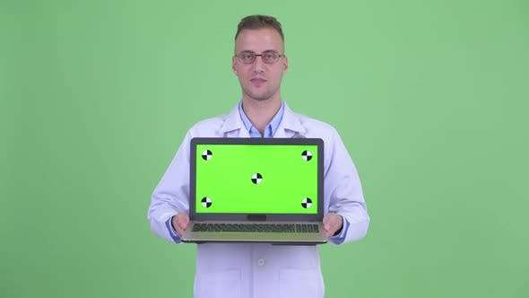 Thumbnail for Happy Handsome Man Doctor Thinking While Presenting with Laptop
