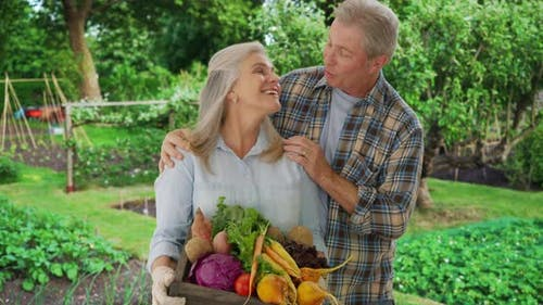 Senior Caucasian couple stands proudly with produce from personal garden