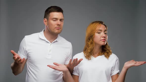 Confused Couple in White T-shirts Shrugging