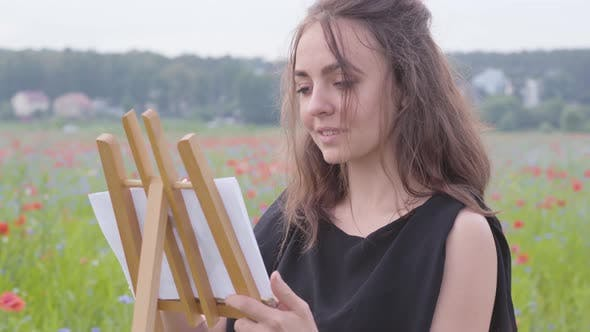 Thumbnail for Portrait of Cute Smilling Girl Painting on the Easel Tanding on the Poppy Field. Young Woman Artist