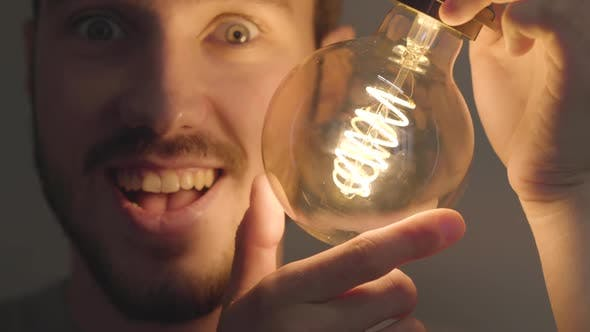 Thumbnail for Close-up of Smiling Bearded Man Screw in and Out a Light Bulb on the Dark Background