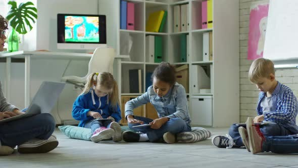 Thumbnail for Preschoolers Using Tablets at Lesson with Female Teacher