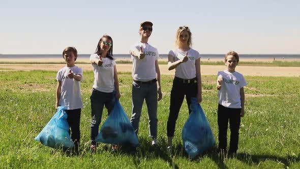 Front View of Young Family Recycle Plastic Bottle Volunteers Posing and Gesturing with Garbage Bags