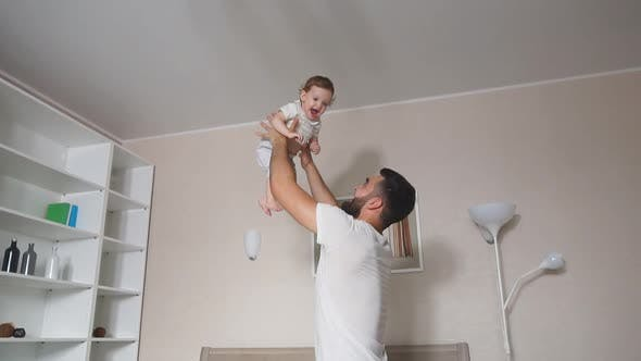 Young Daddy Lifting Daughter Indoors