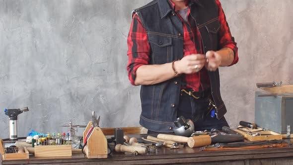 Thumbnail for Junger Handwerker, der nach der Reparatur den Ohrring anprobiert, männlich überprüft den Artikel