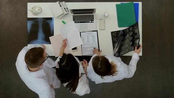 Thumbnail for Team of Doctors Looking at Laptop and Analyzing Xray in Medical Office