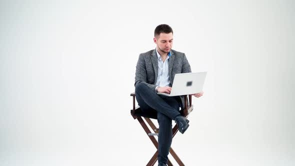 Thumbnail for Young man sitting in a chair with laptop