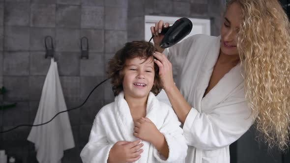 Thumbnail for Young Mom with Long Curly Hair Dries Curly Hair with a Hairdryer Her Little Happy Son