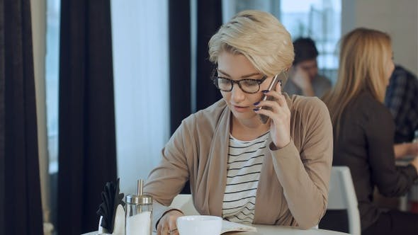Thumbnail for Happy businesswoman talking on the phone in a coffee shop
