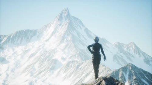 Woman Standing In Snow Wearing Warm Clothes In Mountains