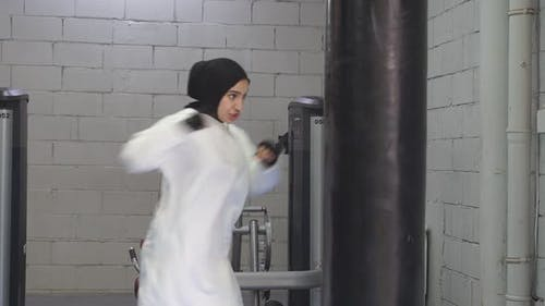 Selbstbewusste Muslima steht in der Pose eines Kämpfers beim Boxen im Fitnessstudio Boxen in der Fitness