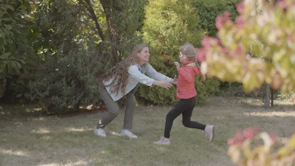 Thumbnail for Little Caucasian Girl in Red Jacket Running To Her Beautiful Smiling Mother in the Park. Woman with