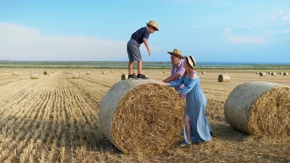 Happy Childhood, Little Boy Playing with His Parents on Field with Bales of Hay