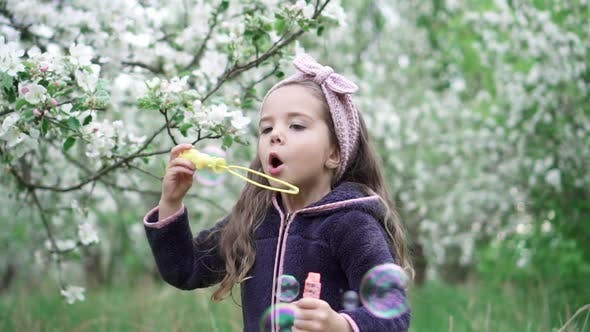 Thumbnail for Happy Little Girl Blowing Soap Bubbles in Spring Garden. Slow Motion