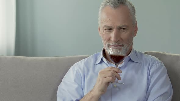 Thumbnail for Grey-haired man sitting on couch and holding glass of wine, enjoying its smell