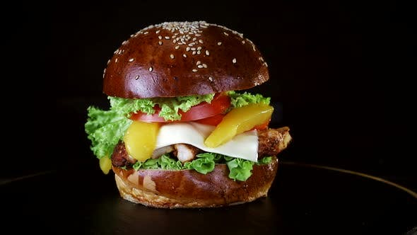 Thumbnail for Burger with a large piece of meat, greens and cheese are spinning on a wooden Board