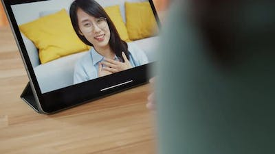 Over the shoulder shot of Asian woman video calling on tablet