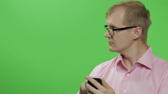 Thumbnail for Caucasian Man Scrolling, Texting on the Smartphone. Place for Your Logo or Text